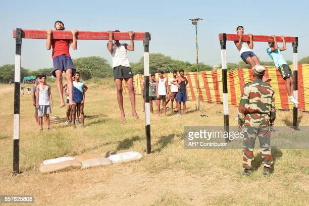 An Indian army officer watches candidates perform pullups during a physical fitness test at an Indian Army recruitment rally at Khasa some 15Kms from...