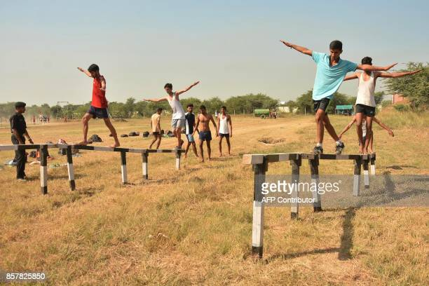 An Indian army officer watches candidates walk on a balance beam during a physical fitness test at an Indian Army recruitment rally at Khasa some...