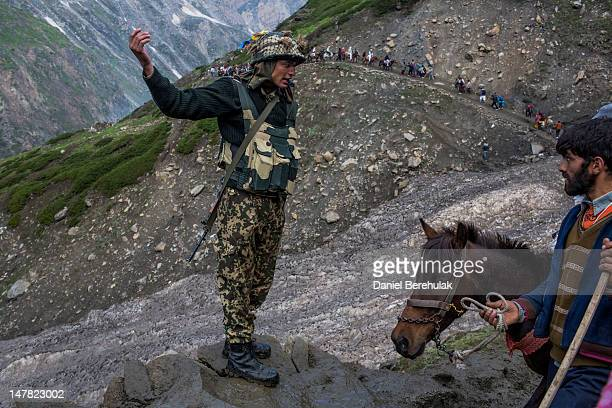 An Indian Army soldier directs Hindu pilgrims and their Kashmiri guides as they make their pilgrimage to the sacred Amarnath Cave one of the most...