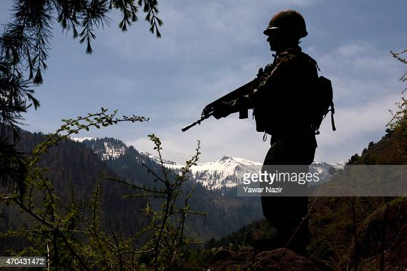 An Indian army soldier is silhouetted against the snow capped mountains of Pakistan administered Kashmir as he guards the the Line Of Control on...