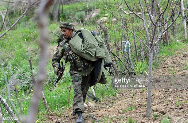 An Indian Army soldier runs as Indian soldiers open fire in the air to disperse thousands of Muslims who snatched the bodies of two militants killed...