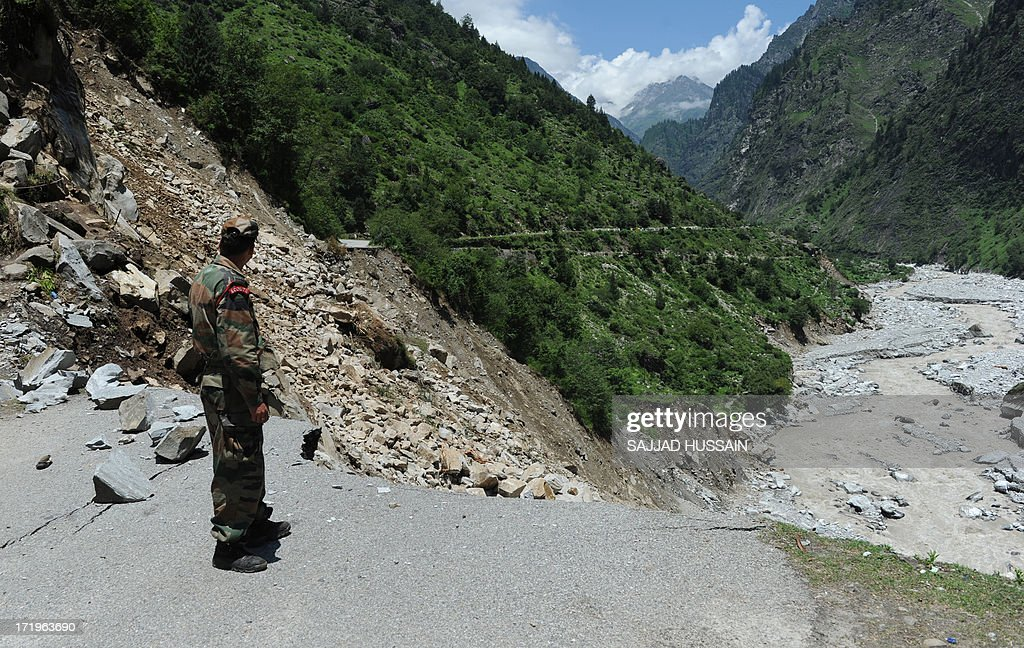 An Indian army soldier stands on a damaged road leading towards Badrinath at Govindghat following flash floods in northern Uttarakhand state, on June 30, 2013. Some 3,000 tourists and pilgrims remain missing in India's flood-ravaged north two weeks after the tragedy, but it is unclear how many of those have been killed, a top state official said June 30.