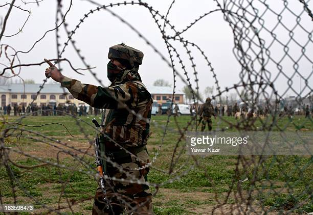 An Indian army soldier stops journalists from taking pictures after an attack on Indian forces by rebels caused a gunfight between the two sides near...