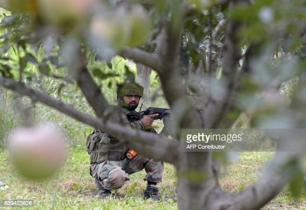 An Indian army soldier takes a position in an apple orchard while a gunfight takes place between militants and government forces in Pulwama south of...
