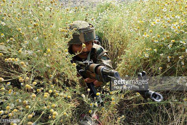 An Indian army soldier takes position at the scene of a deadly attack by armed rebels on the outskirts of Srinagar on June 24 2013 Four soldiers were...