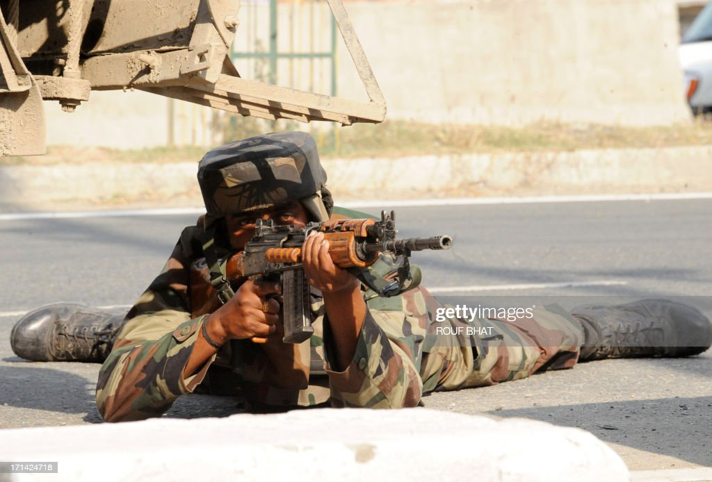 An Indian army soldier takes position at the scene of a deadly attack by armed rebels on the outskirts of Srinagar on June 24, 2013. Four soldiers were killed and six others were wounded in an attack on a convoy in Indian Kashmir on the eve of a visit by Prime Minister Manmohan Singh, the army said. AFP PHOTO/ Rouf BHAT