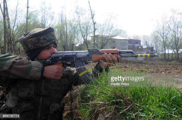 An Indian army soldier taking position to fire towards gun battle site in Chadoora area of Central Kashmirs Budgam district One militant and three...