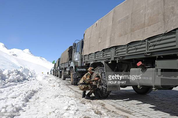 An Indian army solider attaches snow chains to his truck on the SrinagarLeh highway in Zojila Pass about 108 kms 67 miles east of Srinagar on April 6...
