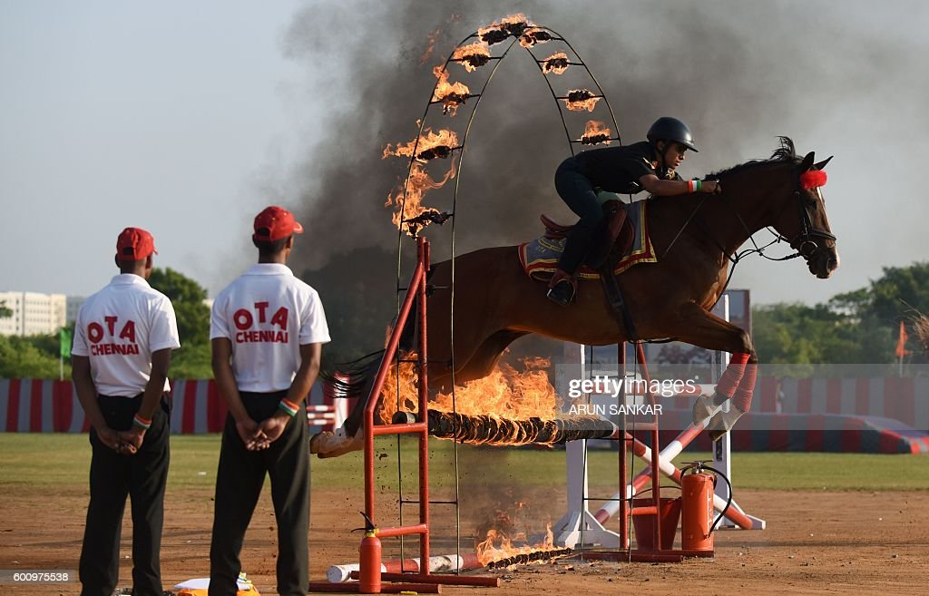 TOPSHOT - An Indian army training cadet rides a horse as they jump through a ring of fire during a combined display at an Officer Training Academy in Chennai on September 9, 2016, ahead of a visit by India's President Pranab Mukherjee who is scheduled to review a passing out parade of cadets on September 10. / AFP / ARUN SANKAR        (Photo credit should read ARUN SANKAR/AFP/Getty Images)