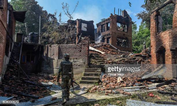 An Indian army trooper inspects war ravaged houses where from rebels were fighting with them after a gun battle on July 4 2017 in Bahmnoo 60 km south...