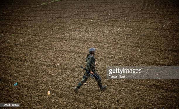 An Indian army trooper rushes towards gun battle site during a heavy exchange of fire between suspected rebels and Indian government forces during a...
