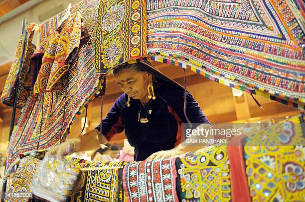 An Indian artisan from Gujarat's remote Kutch region arranges hand made traditional fabrics on the second day of 'Craftroots Festival 2012' at The...