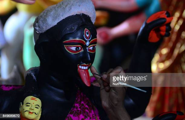 An indian artisan gives final touch to the clay idols of Indian hindu Goddess Kaliin a workshop ahead of Navratri and Durga pooja festival in...