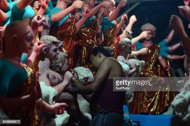 An indian artisan gives final touch to the clay idols of Indian hindu Goddess Durga in a workshop ahead of Navratri and Durga pooja festival in...