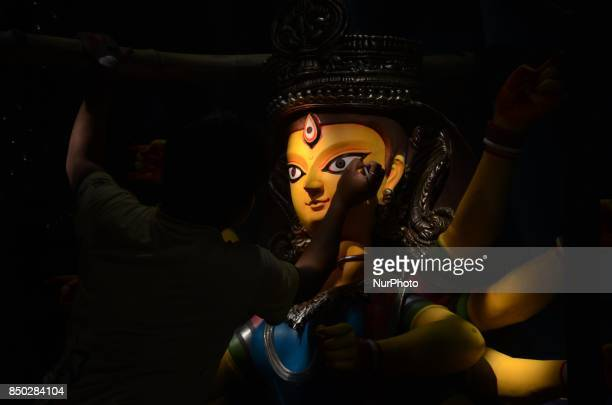 An Indian artisan gives the final touch on goddess Durga in a puja pandal or temporary platforms ahead of Durga Puja festival in Kolkata India on...