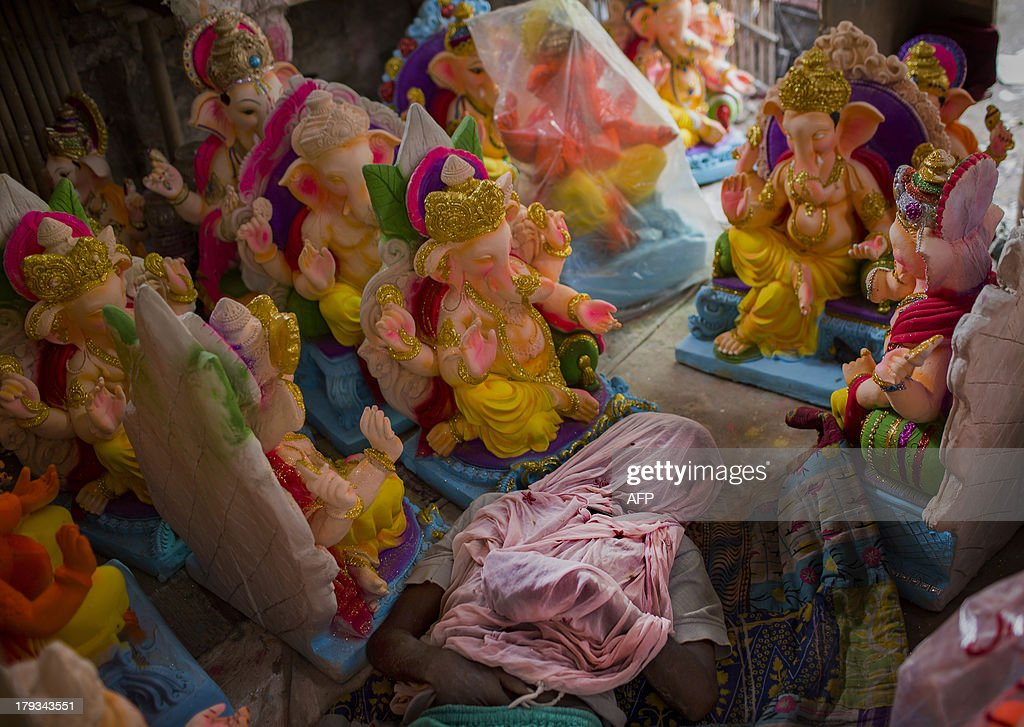 An Indian artisan sleeps with mosquito netting on his face surrounded by Ganesh statues ahead of the Ganesh Chaturthi festival in New Delhi on September 2, 2013. The Hindu festival which celebrates the rebirth of the God Lord Ganesha, starts September 9 and culminates on September 19, with many of the statues being immersed in bodies of water. AFP PHOTO/Andrew Caballero-Reynolds