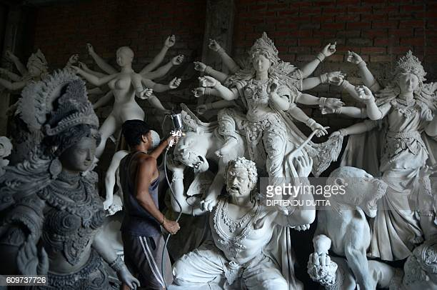 TOPSHOT An Indian artisan works on semifinished clay idols of Hindu goddess Durga inside his workshop in Kumartoli the idol makers' village of...