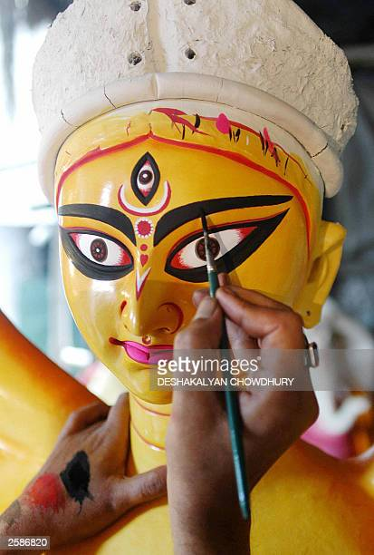 An Indian artist adds finishing touches to the face of an idol of the Hindu goddess Durga at Kumartoli the artist''s village in Calcutta 29 September...