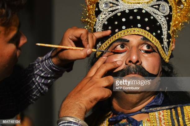 An Indian artist dressed as Ravan gets his makeup done before performing the 'Ramleela' the story of Lord Rama ahead of the Hindu festival of...