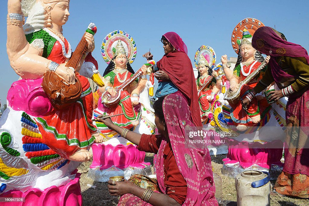 An Indian artist Fulkie (C), Dariya (R), and Gheeci (L) paint idols of the Hindu goddess Mata Saraswati on the outskirts of Amritsar on February 8, 2013. The idols are in heavy demand ahead of the forthcoming Hindu festival of Basant Panchami which falls this February 14. AFP PHOTO / NARINDER NANU