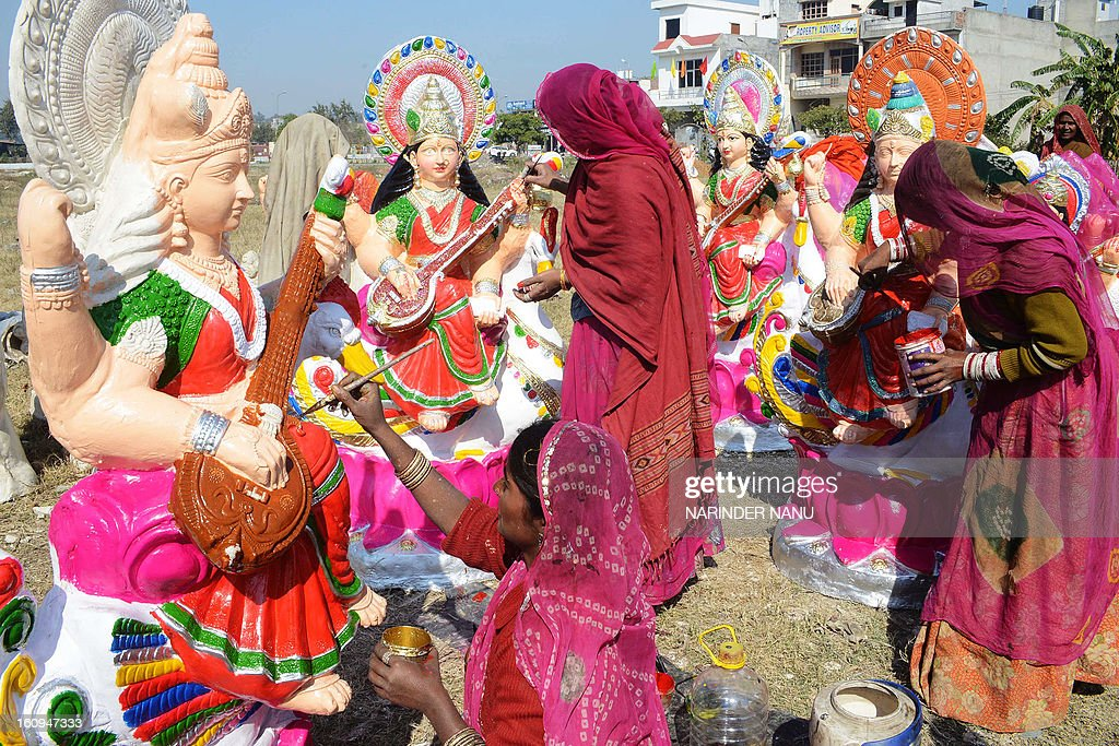 An Indian artist Fulkie (C), Dariya (R), and Gheeci (L) paint idols of the Hindu goddess Mata Saraswati on the outskirts of Amritsar on February 8, 2013. The idols are in heavy demand ahead of the forthcoming Hindu festival of Basant Panchami which falls this February 14.