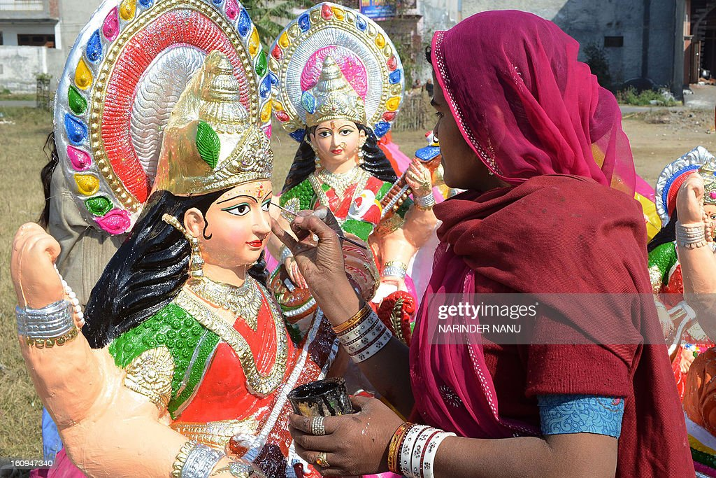 An Indian artist Fulkie (R) paints idols of the Hindu goddess Mata Saraswati on the outskirts of Amritsar on February 8, 2013. The idols are in heavy demand ahead of the forthcoming Hindu festival of Basant Panchami which falls this February 14.