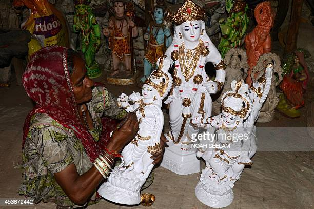 An Indian artist gives the final touches to a statue of the Hindu God Lord Krishna at a roadside stall in Hyderabad on August 16 ahead of The...