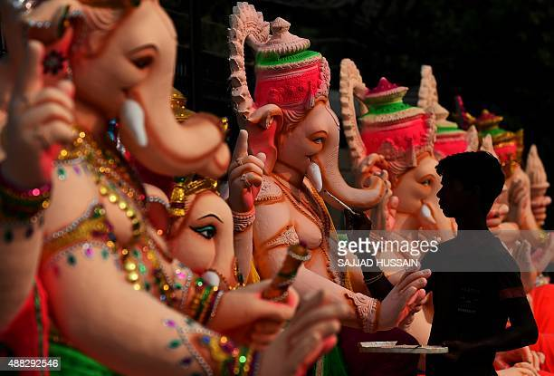 An Indian artist gives the finishing touches to a figure of the elephantheaded Hindu god Ganesha at a workshop ahead of the Ganesh Chaturthi festival...