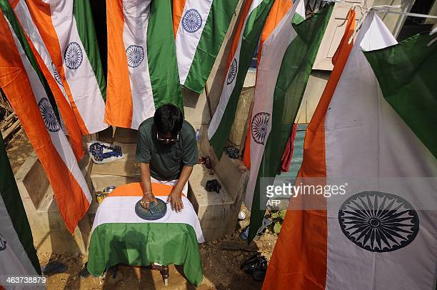 An Indian artist prepares a national tricolour flag for the upcoming Republic Day celebrations at Agartala the capital of northeastern state of...