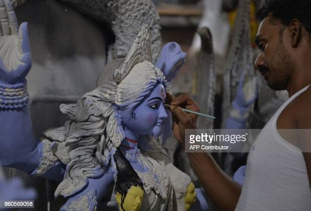 An Indian artist works on a semifinished clay idol of the Hindu Goddess Kali in Siliguri on October 12 2017 Kali worship will take place on October...