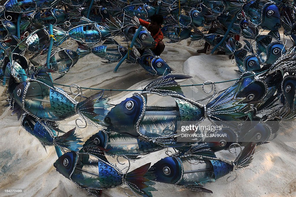 An Indian artist works on a series of fish made out of metal sheets to decorate a Pandal (temporary worship place) made to worship Hindu goddess Durga, and to create awareness about the marine life and marine eco-system among the visitors, for the upcoming Hindu festival Durga Puja in Kolkata on October 17, 2012. The five-day period of worship of Durga, who is attributed as the destroyer of evil, commences on October 20. AFP PHOTO/Dibyangshu SARKAR