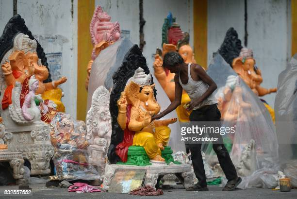 TOPSHOT An Indian artist works on an idol of the elephantheaded Hindu god Lord Ganesha ahead of the Ganesh Chaturthi festival at a roadside in...