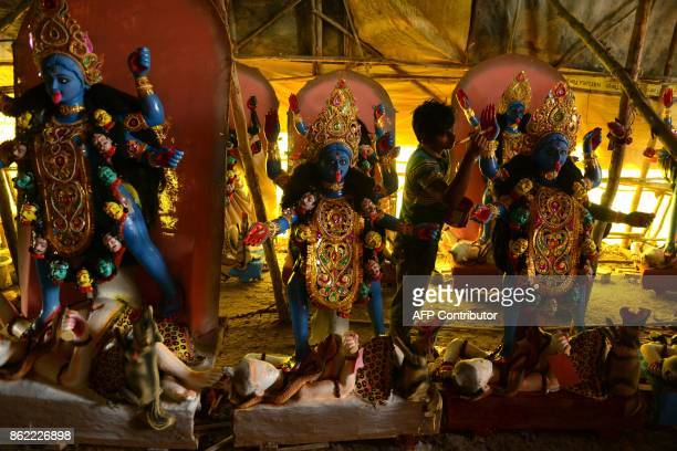 TOPSHOT An Indian artist works on an idol of the Hindu Goddess Lakshmi and Kali at a workshop in Hyderabad on October 17 2017 Diwali the Hindu...