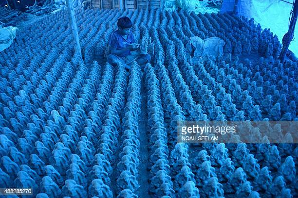 An Indian artist works on ecofriendly figures of Hindu God Lord Ganesh made with mud jute and bamboo at a blue tarpcovered workshop on the outskirts...