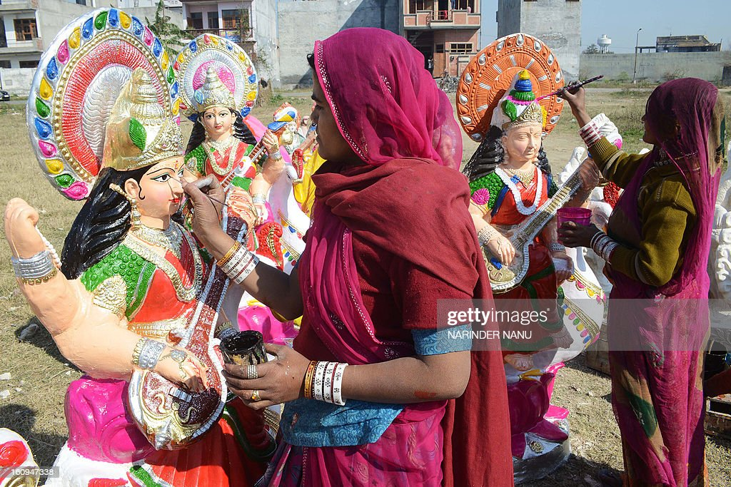 An Indian artists Fulkie (L), and Dariya (R) paint idols of the Hindu goddess Mata Saraswati on the outskirts of Amritsar on February 8, 2013. The idols are in heavy demand ahead of the forthcoming Hindu festival of Basant Panchami which falls this February 14. AFP PHOTO / NARINDER NANU