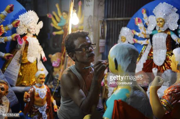 An Indian artists gives finishing touches to a clay statue of Hindu goddess Durga at his workshop in Siliguri on September 23 2017 The fiveday Durga...