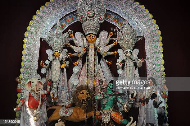 An Indian artists prepares an idol of Hindu goddess Durga being displayed for the upcoming Hindu festival Durga Puja in Kolkata on October 19 2012...