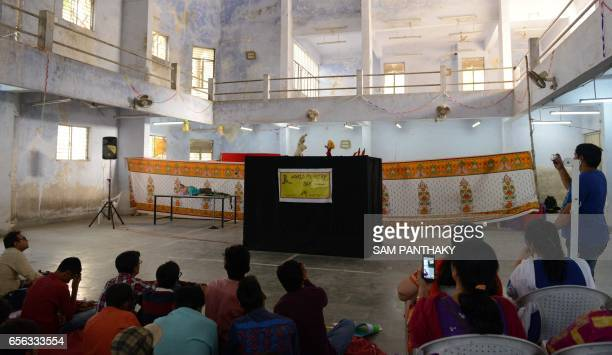 An Indian audience look on as puppeteers from 'Meher' The Troupe group put on a show during a workshop on the occasion of World Puppetry Day in...