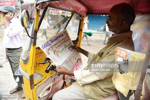 An Indian auto driver reads a newspaper reporting on the newlyformed Telangana state's first Chief Minister K Chandra Sekhar Rao taking office in...