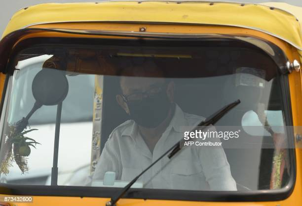 An Indian auto driver wears a protection mask amid heavy smog on a street in New Delh on November 13 2017 Schools reopened in New Delhi on November...