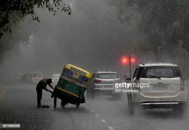 TOPSHOT An Indian auto rickshaw driver tries to repair his vehicle after it broke down in heavy rain in New Delhi on August 23 2017 / AFP PHOTO /...