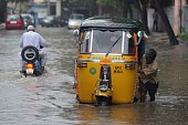 An Indian autorickshaw driver pushes his three wheeler through water logged streets during heavy rains in Hyderabad on October 9 2013 Andhra Pradesh...