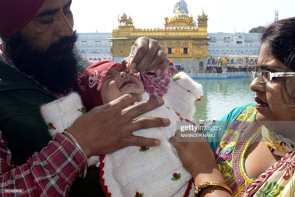 An Indian baby girl receives polio vaccination drops from a medical volunteer during an immunisation drive outside the Golden Temple in Amritsar on February 24, 2013. The number of polio cases worldwide reached a record low in 2012, giving experts confidence that the disease can finally be eradicated, according to presentations made November 2012 at a major US conference.