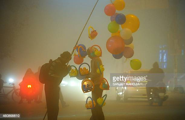 An Indian balloon vendor plys his trade along a fog affected road in Allahabad on December 28 2014 Many parts of northern India are experiencing...