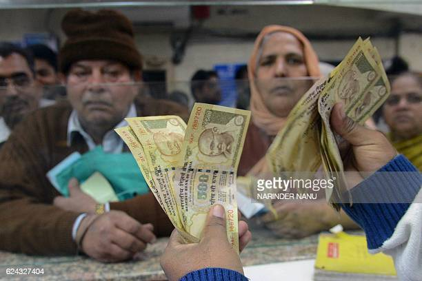 An Indian bank teller counts out notes as senior citizens gather inside a bank as they wait to deposit and exchange 500 and 1000 rupee notes in...