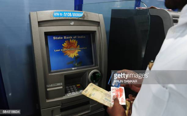 An Indian banking customer draws cash from an ATM in Chennai on July 29 2016 Banking operations across the country were affected as employees in 40...