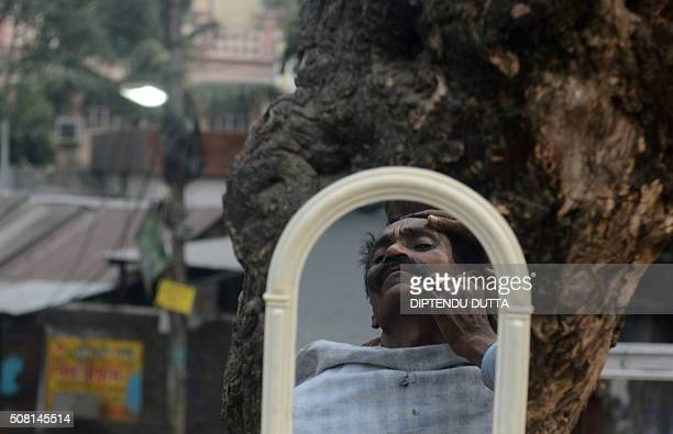 TOPSHOT An Indian barber tends to a customer at his roadside shop in Siliguri on February 3 2016 AFP PHOTO / Diptendu DUTTA / AFP / DIPTENDU DUTTA