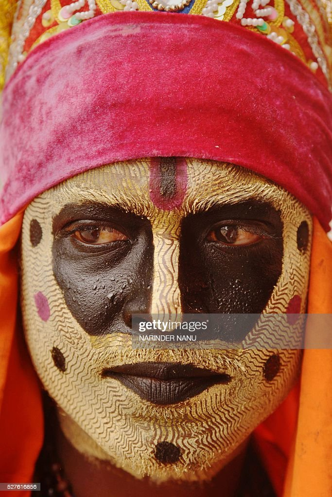 An Indian beggar known as a behrupiya (a person who assumes various characters) poses for a photograph with his face painted to depict the Hindu Lord Hanuman as he begs for alms at the roadside in Amritsar on May 3, 2016. / AFP / NARINDER