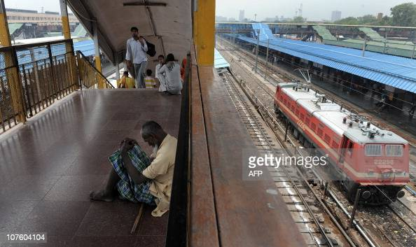 An Indian beggar sits on a platform as a train engine passes at the New Delhi Railway Station in New Delhi on July 3 2009 Railways Minister Mamata...