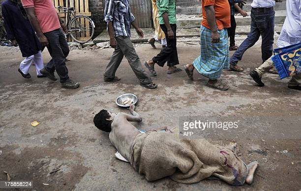 An Indian beggar waits for donations as Muslim devotees walk towards EidUlFitr prayers at a mosque in Agartala on August 9 2013 Muslims around the...